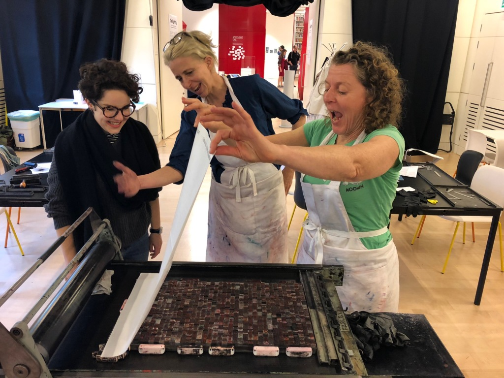 Three women lift a sheet of paper off a printing block of text in a letterpress workshop at the Wellcome Collection.