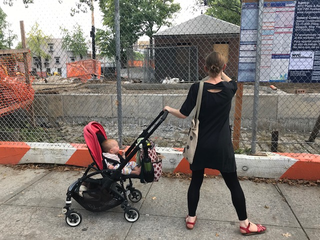 a red pram with a baby in it, held to the side of a woman dressed in black, standing in the street in new york city