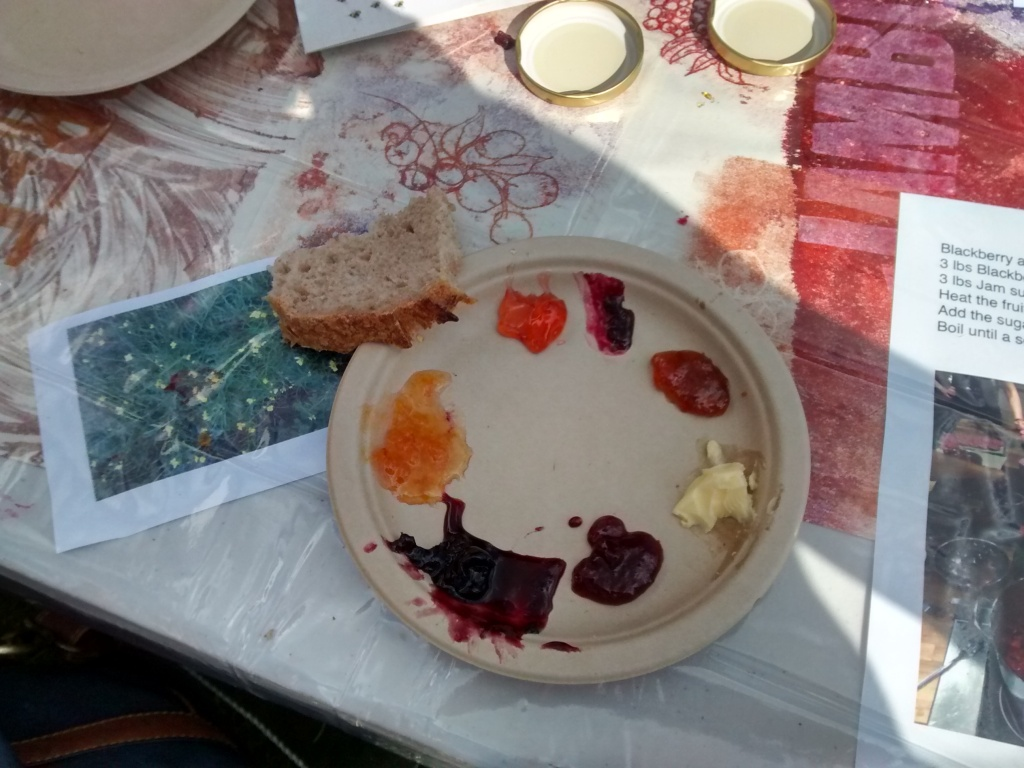 a round brown plate with blobs of different coloured jam on it