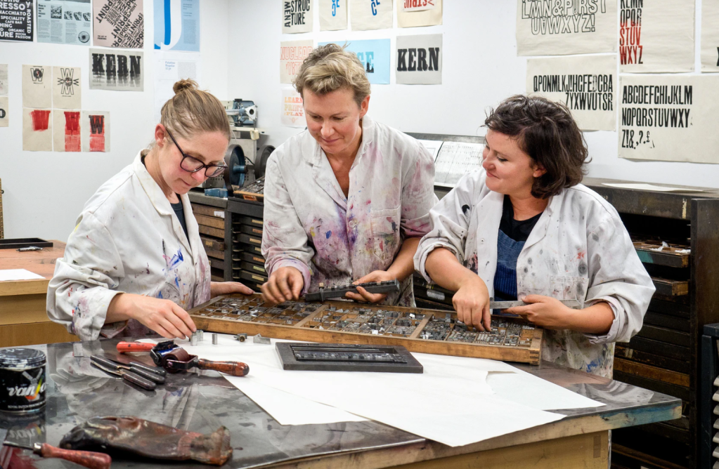 three women stand at a table working with letterpress type. photo David Sandison.