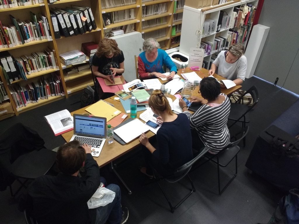 a group of people sit at a table in LADA's study room editing wikipedia