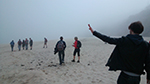 people walking on a beach in the mist