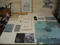 work table with text works 'mitten, midden, mire mirth' and Ci/SfB sculpture, text work 'The Devil is in the Detail'