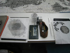 work table showing 'letters from the bank' and two commemorative handkerchiefs - pencil on cloth hanky, and ink on paper hanky