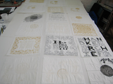 work table showing commemorative handkerchiefs - ink, pencil and laser cut paper hankies