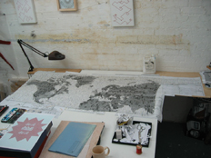 work table showing 'Letters from the bank' and red embroidery on graph paper