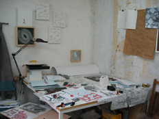 studio wall showing embroidered canvases, ink on paper drawings, and work table with red embroidery on graph paper