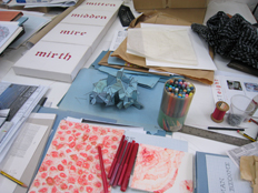 work table with Ci/SfB sculpture, 'Mitten, Midden, Mire, Mirth' text work, drawing in red ink on paper.