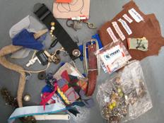 scraps of material and sewing box ephemera, buckles, labels, rivets