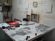 work table with 'letters from the bank' red embroidery on graph paper, box framed paper sculptures and embroideries on canvas