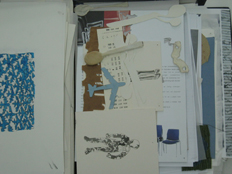 box file with small works on paper including 'beds of bethnal green' drawing, a blue aeroplane, and a teaspoon covered in cloth.
