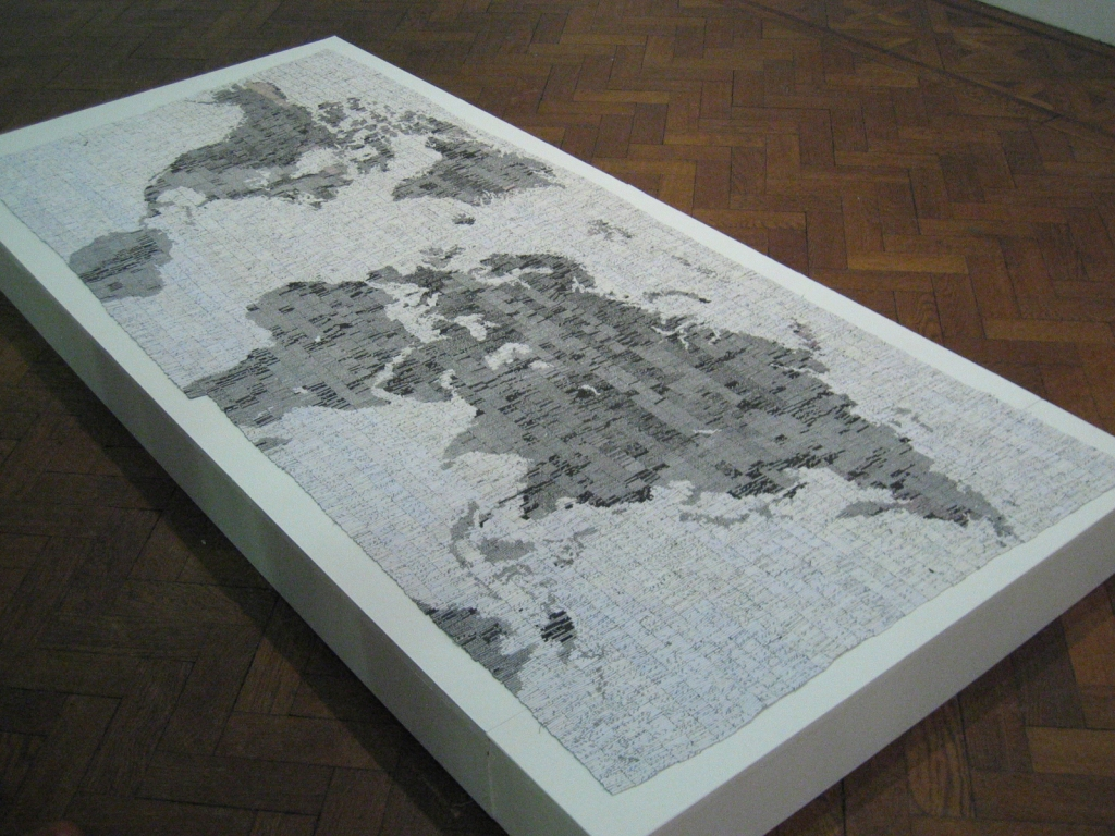 a large incomplete map of the world in black and white on a raised white plinth above a wooden floor.